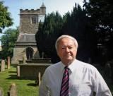 Dr John Jones in churchyard of St Cross, Holywell